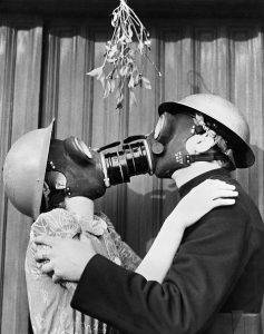 (Original Caption) 1/11/1940-London, England- Strictly as a gag, these Londoners posed for this picture to show the extent to which air raid precautions in England thwarted the romantic influence of mistletoe around Christmastime. It is pointed out in the British caption that, after posing for the picture, the subjects took off the masks and did the sprig justice.